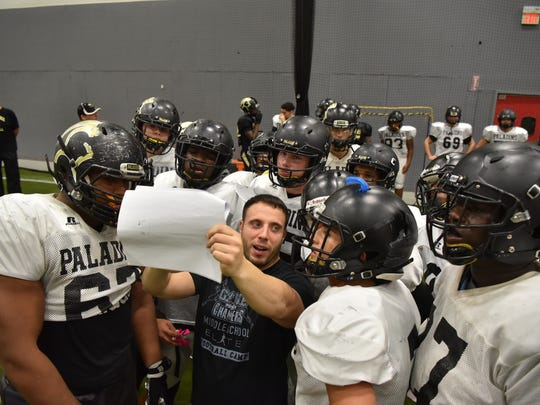 Coach Greg Russo works with players at Paramus Catholic football practice on Tuesday.