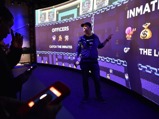 MC Pete Vigeant leads the gamers trough the game at the The ESC Game Theater in Garden State Plaza, on Wednesday. The ESC Game Theater, first of its kind, is an interactive high-tech experience where up to 30people can play a game on a big screen using touch devices as controllers.