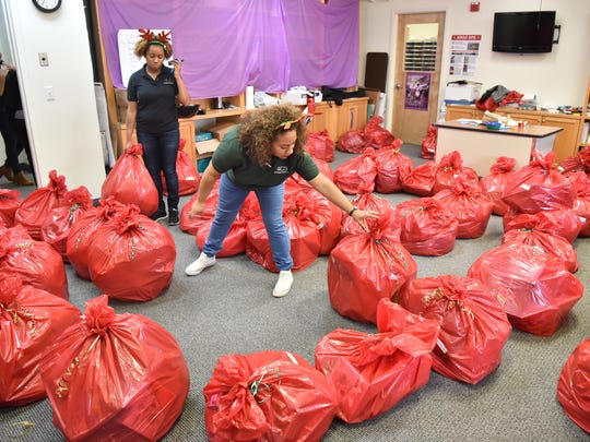 Volunteers Jennifer Garcia and Denis Hunt distributing bags of clothing  for children in Paterson on Saturday.