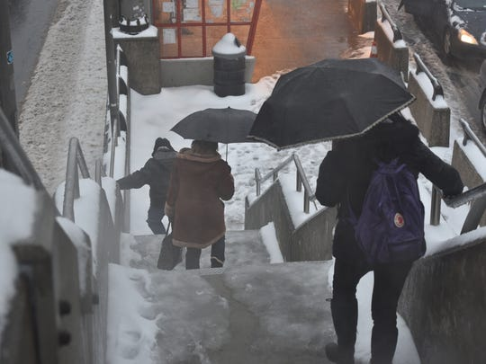 Commuters to New York City navigate icy steps at George Washington Bridge bus stop on Saturday.
