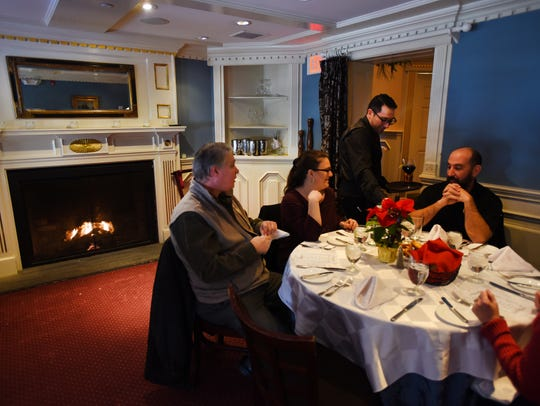 Photo of guests near the fireplace during the lunch