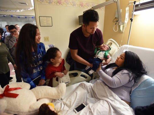 Bryan Preciado of Totowa and his wife, Anaika Santillana, holding baby Bryan Chris on Sunday as family members looked on.