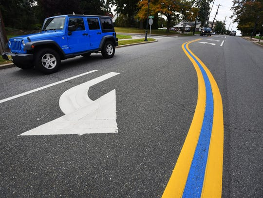 A blue line painted between the double yellow lines to show support for police officers.