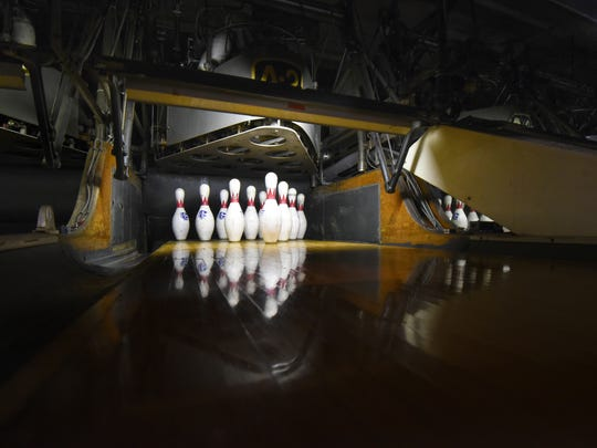 Bowling pins sit motionless in a quiet Park Lanes Bowling Alley.