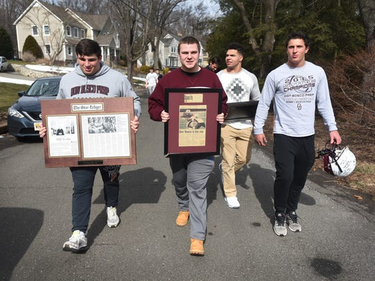 A group of current  Don Bosco football players are seen carrying some belongings of their former coach Greg Toal's to his house on Sunday morning, Feb. 19, 2017 as a show of support for their coach, who they feel was wrongly forced to resign by school officials.