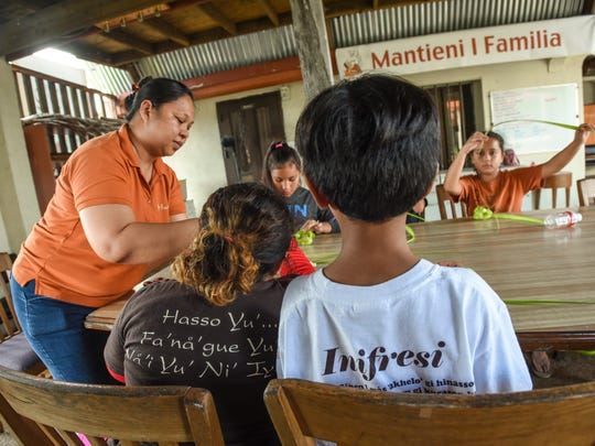 Saina Donna Cruz, left, teaches young students how to weave with coconut leaves at the Chief Hurao Academy in Hagåtña in March 9, 2017.