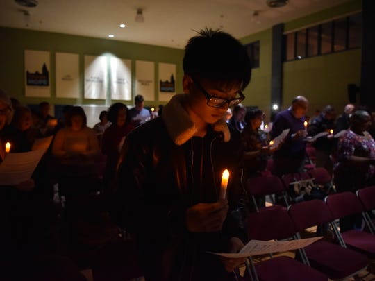 Mike Hong of Bogota holds a candle during a worship service on Wednesday, March 22, 2017 at First Presbyterian Church of Englewood. Members old and new came to commemorate the year since a fire devastated the sanctuary.