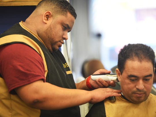 Owner Alberto Marte trims the hair of his worker Juan Burgos at Aquilino's Barber Shop in Passaic in March.