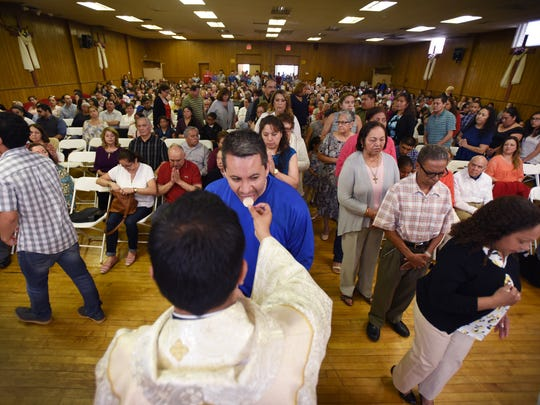 Father Duberney Villamizar gives Communion during Easter