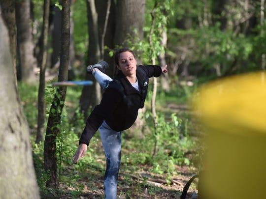 Dina Napolitano throws a Frisbee at a disc golf course
