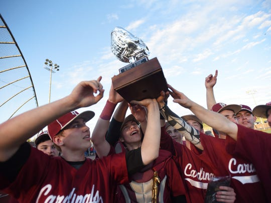 Pompton Lakes pitcher, Christian Ferrara (no. 13, L) who hit  a three run homer to lead the game in the beginning of the sixth inning, holds up the Championship Trophy with his  teammates as they celebrate their victory over Passaic Tech for the Passaic County baseball tournament championship game at Passaic Tech's field in Wayne on May 16th, 2017. Pompton Lakes defeated Passaic Tech 10 to 6 and won the championship.