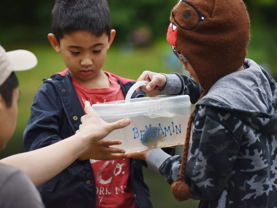 Benjamin and Sam Guanzon, along with their dad Derrick, check the status of a fish they just caught at the Parks & Recreation Trout Fishing Contest in Nutley on Saturday, May 20.
