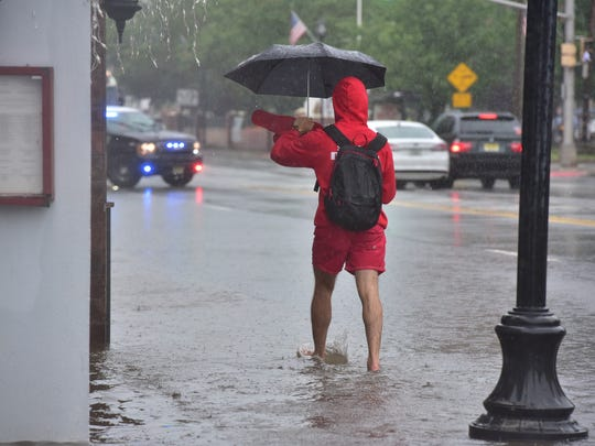 An unidentified man crosses the flooded sidewalk on River road in Edgewater. Marko Georgiev/NorthJersey.com