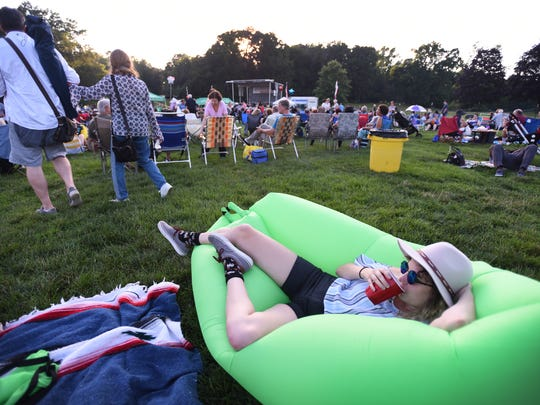 """Laura Clark of Montclair lies on a temporary inflated bed called """"Hangout Bag"""" during the Essex County Free Summer Music Concert prior to the fireworks celebration at Brookdale Park in Montclair on July 3rd, 2017."""