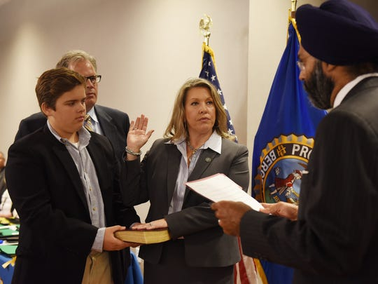 Carol Novey Catuogno is sworn in as Executive AP by Prosecutor Gurbir S. Grewal, as her husband David and son Lucas look on during the Bergen County Prosecutors' Swearing-in Ceremony at Two Bergen County Plaza Conference Center in Hackensack on July 17th, 2017.