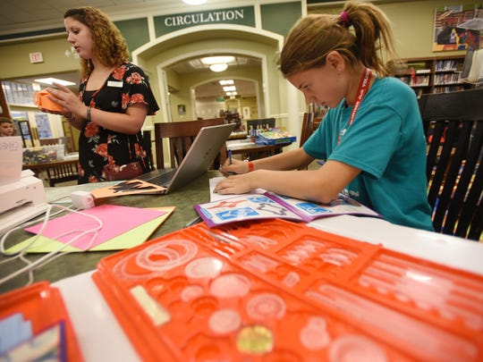 Casey Roberts (age 11), a volunteer, plays with Spirograph as Morgan Taylor (far L), Teen & Technology Librarian leads the program that allows children to experiment with various technology and create things, photographed at Glen Rock Public Library on July 18th, 2017.