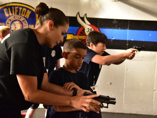 Detective Carmen Bermudez works with junior recruits at the gun range. The Clifton Police Department held its first junior police academy, a week-long program that completed on Friday.