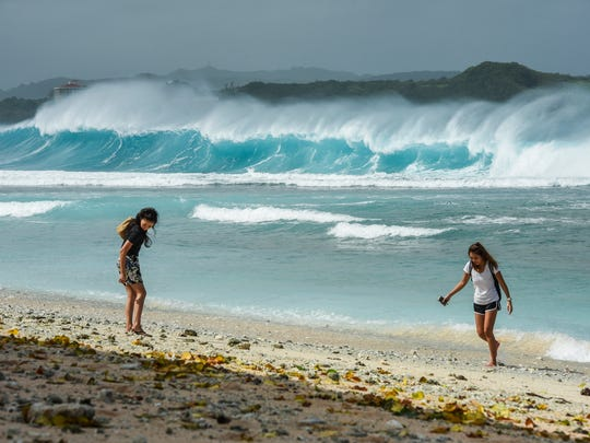 Huge waves crash onto the submerged reef in Tumon Bay as beachcombers search for shells and other items washed ashore by the wave action on Tuesday, Oct. 24, 2017.