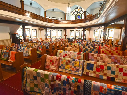 Quilts cover every pew of St. Mark's Lutheran Church on Wednesday. They will be blessed on Sunday before they are distributed.