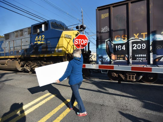 As a train goes by in Bergenfield, a member of a coalition of New Jersey organizations holds up a placard during a rally Sunday to demand that CSX provide information about oil trains passing through densely populated North Jersey.