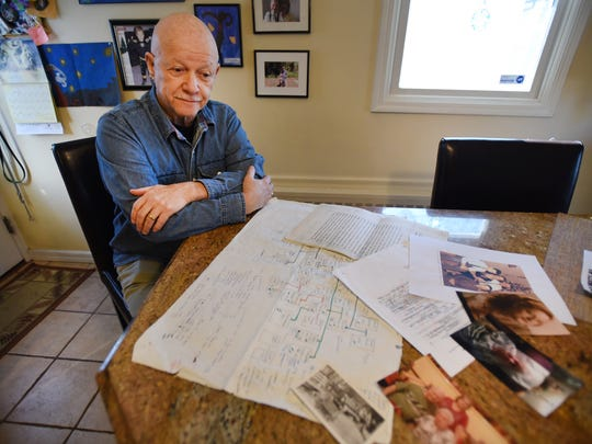 Photo of Bob MacNish with his documents and photos and papers he collected during his search for his birth parents, photographed at his home in New Milford.