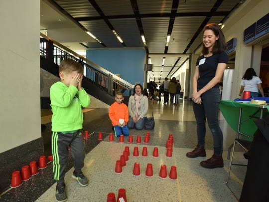 Catherine Fergesen, leads a blindfolded Ethan Massa, age 5, trough a maze of cones in Liberty Science Center. 17-year-old founder Catherine Gonzales Fergesen, right, started STEM Girls for the betterment of STEM education for girls from impoverished communities and under represented backgrounds.