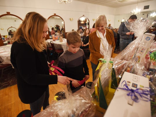 "Rebekah Cusick of Rutherford selects items from the raffle prize with her son, RJ, 9, and her mother, Lisa Oliver, during the first charity event of Buddy Ersalesi Scholarship Fund called ""Board Games and Beefsteak"" at The Elks Club in Rutherford March 25, 2018."