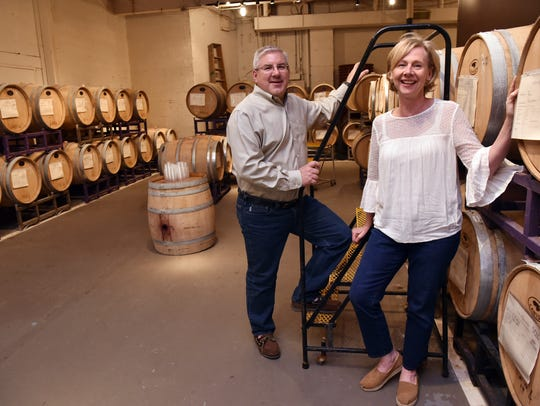 Karla and Craig Cicciari of California WineWorks stand among the barrels of wine at the facility.