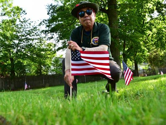 Vietnam Vet James Kim, places a flag on a soldiers