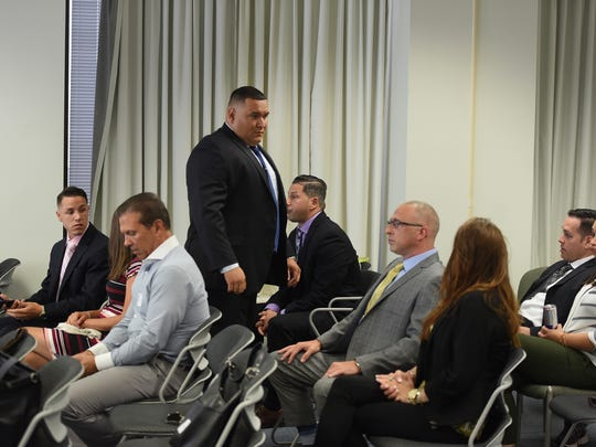 Former members of the Hackensack Police Department, (L to R), Detective Joseph Gonzalez, Officer Victor Vazquez (standing), Detective Rocco Duardo, Sgt Justin de la Bruyere and Detective Mark Gutierrez (2nd from R), are seen in court as they appeal after their dismissal from the Hackensack Police Department prior to the hearing at the Administrative Law Court in Newark on 07/18/18.