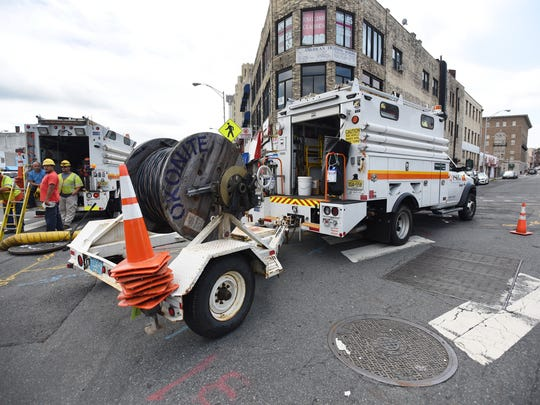 PSE&G crews at the scene of where wiring caught fire down in a manhole where water had collected from the storm in Passaic at Main Avenue and Henry Street on July 22.