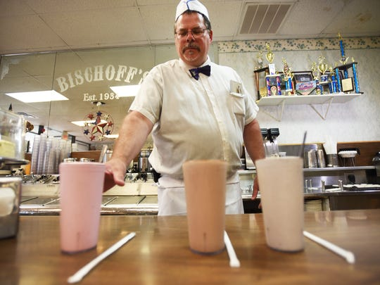 Steven Mather, the grandson of the original owner, places a strawberry milkshake next to a chocolate milkshake (C) and a cookie crush milkshake (R) at Bischoff's in Teaneck on 07/30/18 .