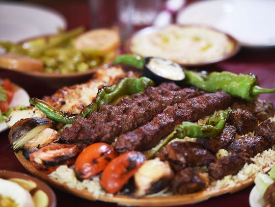 A mixed grill platter of various food is seen on the
