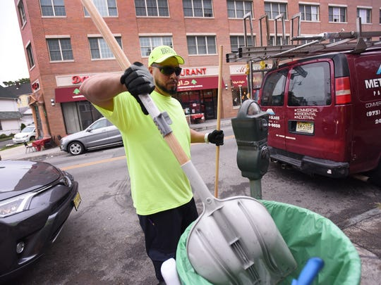 Paterson resident Jeremy Lisowski used a shovel to collect all the trash and litter and deposit it into a garbage bin as he cleans the street near the corner of Main Street and Genessee Avenue in Paterson on Oct. 12.