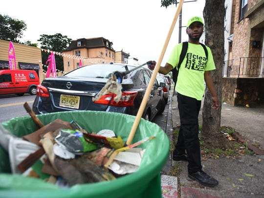 "Paterson resident Andres Scott. 32, is part of the city's part-time ""clean team."" Paterson gave temporary, part-time jobs paying $14.42 to 17 people to clean the streets in about 29 different commercial strips. Mayor Andre Sayegh says he wants to extend the program."
