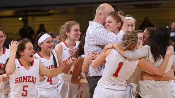 Somers girls basketball head coach Marc Hattem celebrates with players after defeating Eastchester 49-48 to win the  Section 1 Class A championship game at the Westchester County Center in White Plains March 5, 2017.