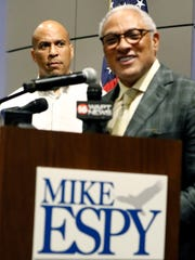 U.S. Sen. Cory Booker, D-N.J., left, watches as Democrat Mike Espy pledges to work across party lines during a brief speech in Jackson, Mississippi on July 20, 2018.