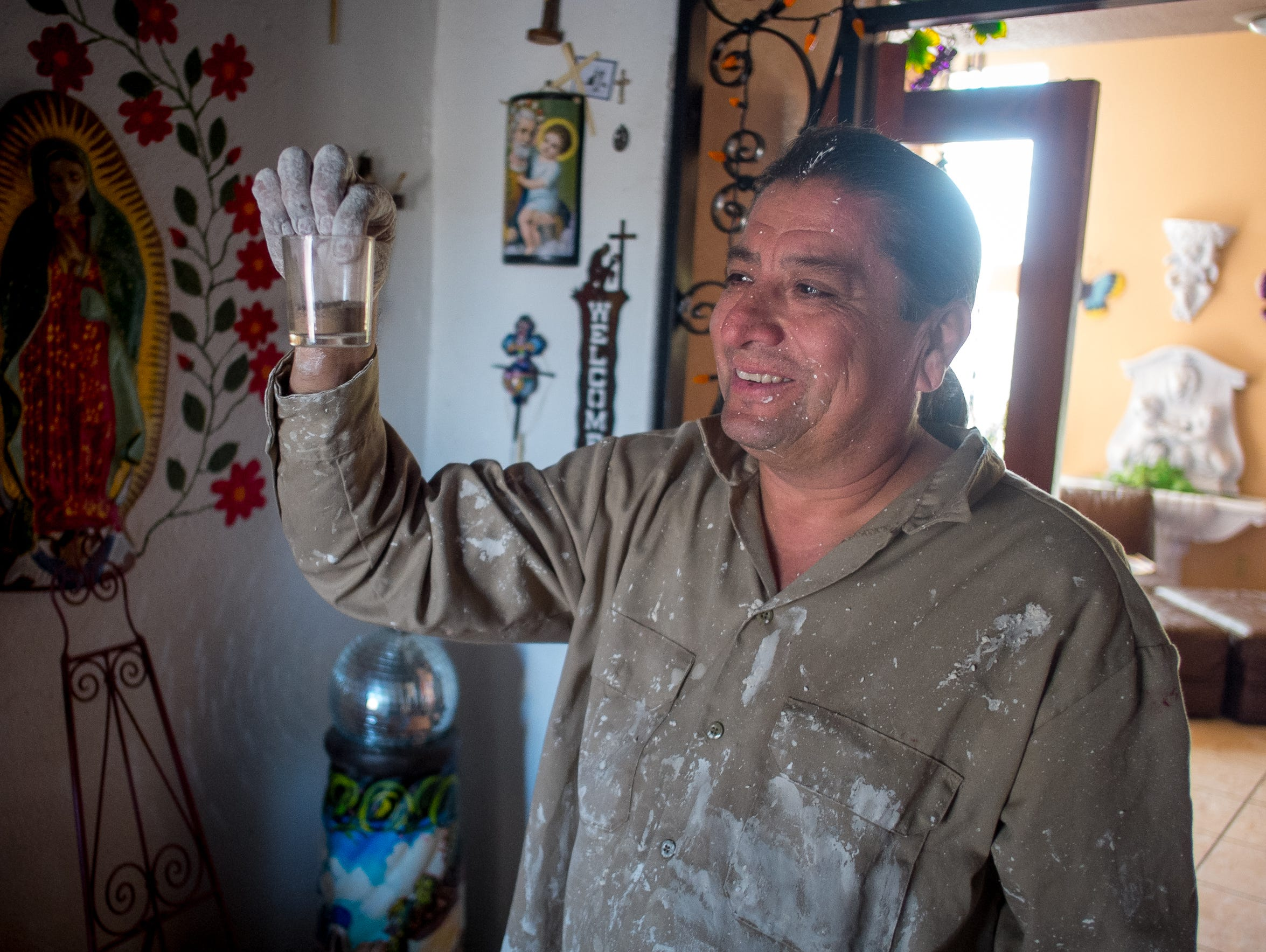 Current home owner Gerald Sánchez, holds up a container