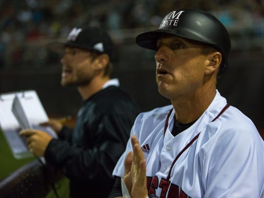 NMSU head baseball coach Brian Green talks to his players from the dugout on Tuesday during the NMSU/ UNM game.