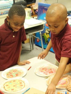 """BRIDGETON - At Quarter Mile Lane School, a kindergarten class celebrated Pi Day by making """"pizza pies."""" Students used paper plates, crayons and their favorite paper pizza toppings. Ma'Kel Childers (left) and Mekhi Brantley are pictured with their """"pizza pies."""""""