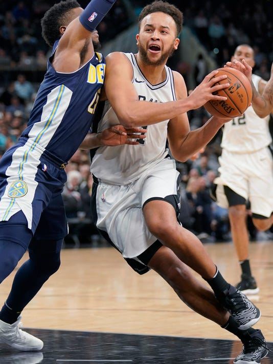 San Antonio Spurs' Kyle Anderson, right, drives against Denver Nuggets' Malik Beasley during the second half of an NBA basketball game Tuesday, Jan. 30, 2018, in San Antonio. San Antonio won 106-104. (AP Photo/Darren Abate)