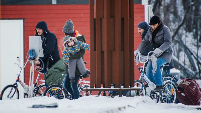 Migrants walk and bike to the Norwegian border crossing station at Storskog after crossing the border from Russia on Nov. 12, 2015.