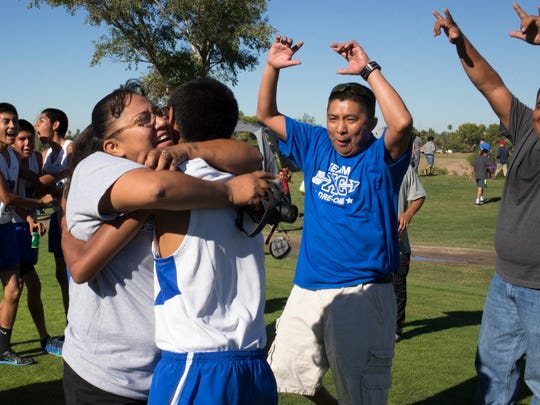 Andre Lucas gets a hug from his aunt Clarissa Tungovia after Hopi won its 25th straight Div. IV boys cross country championships on Nov. 8, 2014, at Cave Creek Golf Course in Phoenix.