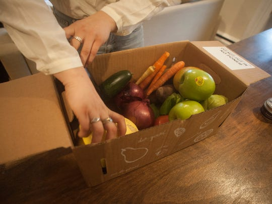Emily Coch sorts produce at her Philadelphia home after a delivery from Hungry Harvest.