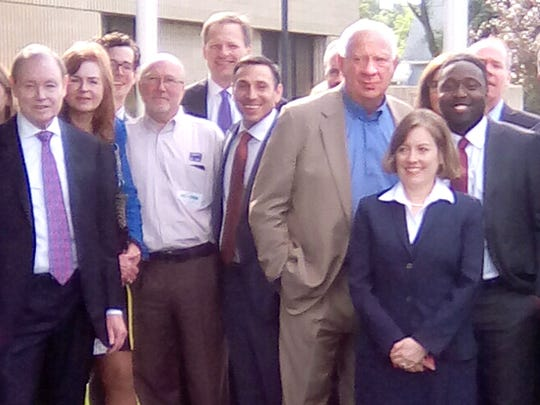 BPI owner Eldon Roth, center in tan jacket, his wife, Regina, fourth from left, members of the Roth family, BPI officials and lawyers take a group photo Wednesday outside the Union County Courthouse in Elk Point, S.D. The company settled its $1.9 billion defamation lawsuit against ABC and correspondent Jim Avila earlier in the morning.