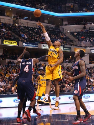 Pacer David West shoots past the Atlanta Hawks' Paul Millsap, left, and Jeff Teague during Indiana's 108-92 loss to the Hawks at Bankers Life Fieldhouse in Indianapolis on Monday, Dec. 8, 2014. West finished with 8 points, 3 assists and 4 rebounds for the Pacers.