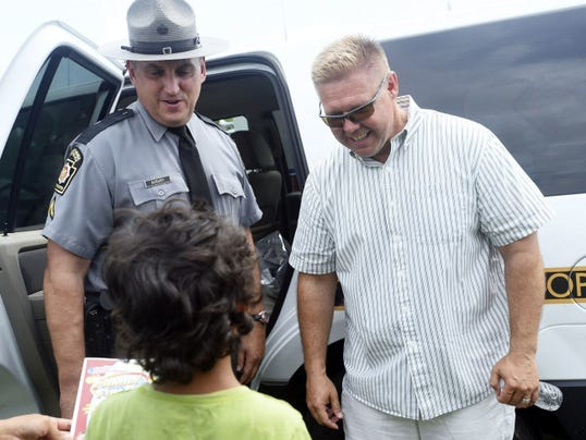 Pennsylvania State Trooper Ed Asbury greets visitors with state Sen. Rich Alloway at Shippensburg Area Chamber of Commerce's inaugural Family Fun Day at the Shippensburg Fairgrounds on Saturday, Sept. 6, 2014.