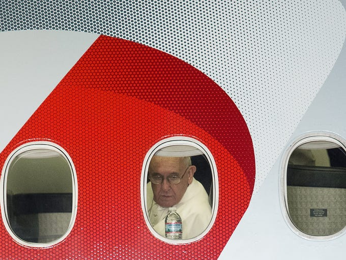 Pope Francis looks out the window of his plane before
