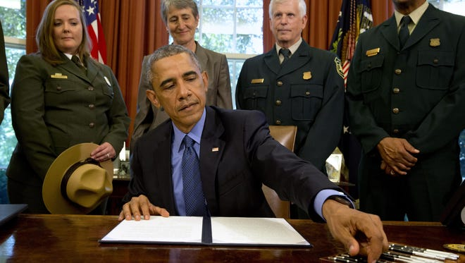 President Barack Obama signs designations for three new national monuments: Berryessa Snow Mountain in California, Waco Mammoth in Texas, and the Basin and Range in Nevada, in the Oval Office of the White House Friday, July 10, 2015, in Washington. Behind him from left are April Slayton, chief of public affairs and chief spokesperson of the National Park Service; Secretary of the Interior Sally Jewell; U.S. Forest Service Chief Tom Tidwell; and Randy Moore, Forest Service.