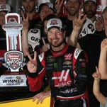 Kurt Busch, driver of the #41 Haas Automation Chevrolet, Gene Haas, co-owner of Stewart Haas Racing, and his team pose in an alternate Victory Lane after winning the NASCAR Sprint Cup Series Quicken Loans 400 at Michigan International Speedway on Sunday.